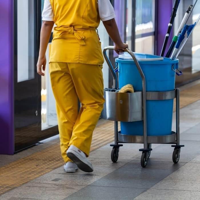 a Janitor psuhing a cleaning cart