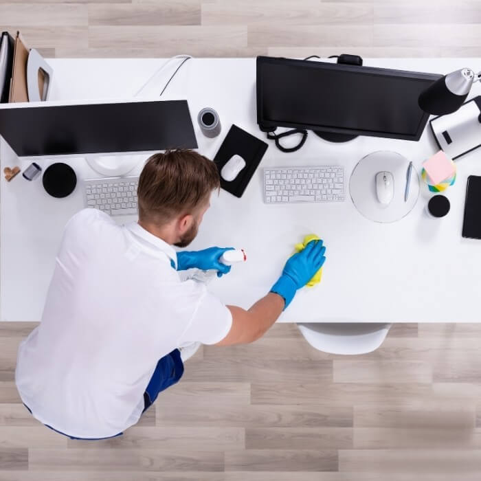 An aerial view of a man cleaning an office table